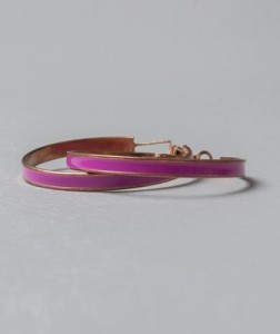 Hoop earrings in a shade of raspberry rose with a gold outline.